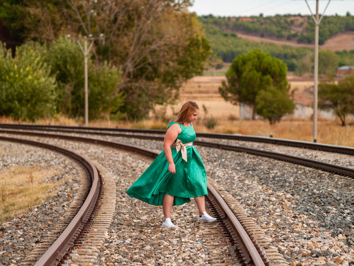 Woman standing on railroad tracks