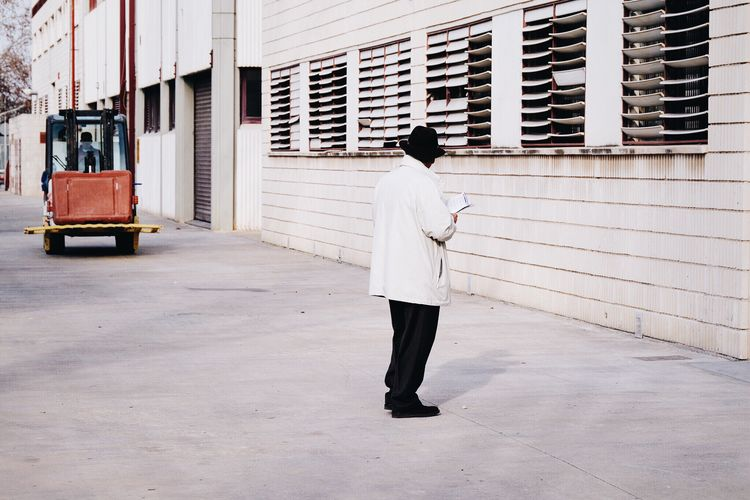 Man Streetphotography Everyday Lives Architecture Every Picture Tells A Story Composition Scene Outdoors Transport Windows White WhiteCollection Minimalism Wall Clothes Adult Perspective Real People Everyday Life Street Photography Driving Building Elegant Street Hat