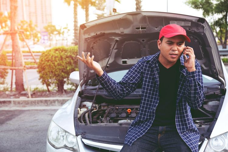 Man talking on phone while standing by broken car