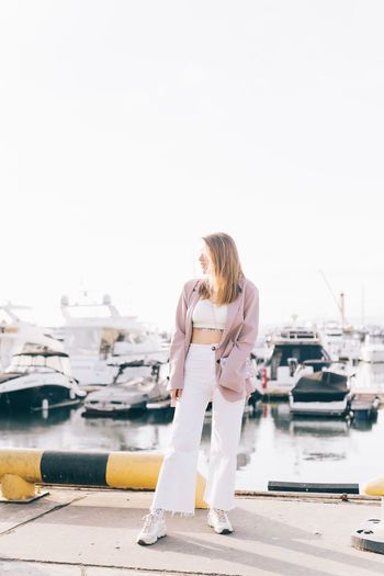 Portrait of a happy cheerful emotional traveling girl in fashionable clothes near yachts and water