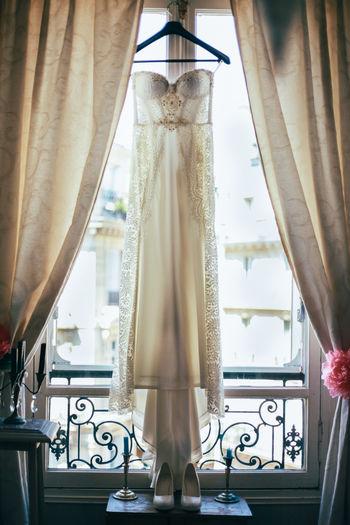 Wedding dress hanging on window at home