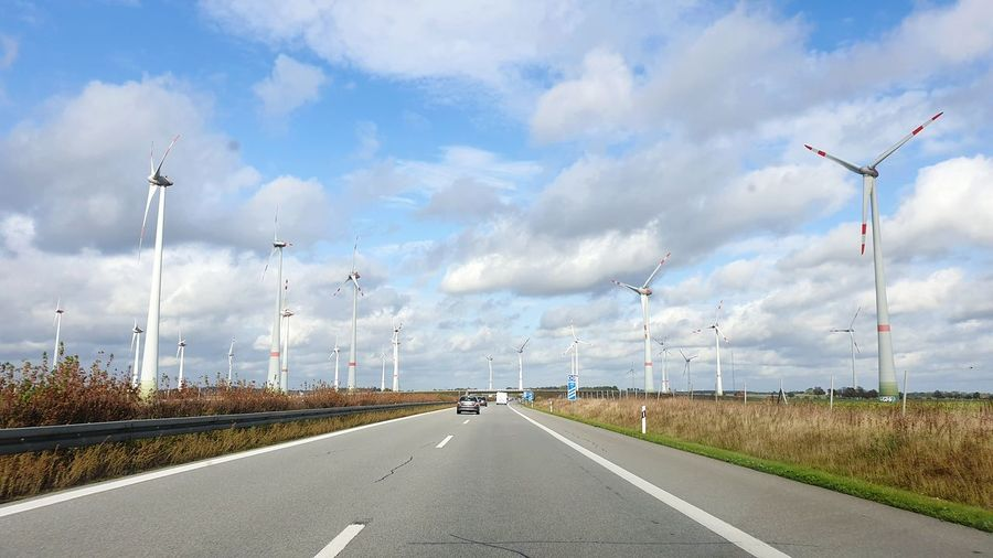 Road by wind turbines against sky