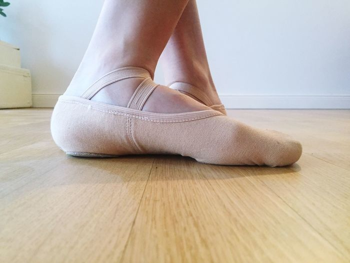 Low Section Of Person Wearing Ballet Shoes On Hardwood Floor