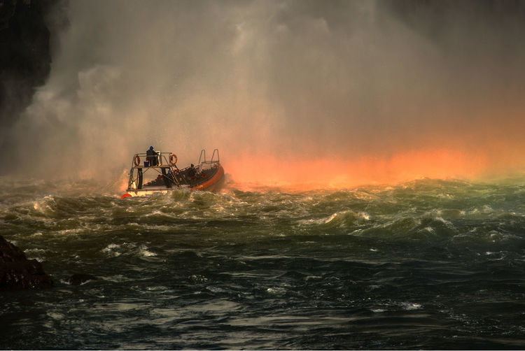 Boat sailing in sea against waterfall during sunset