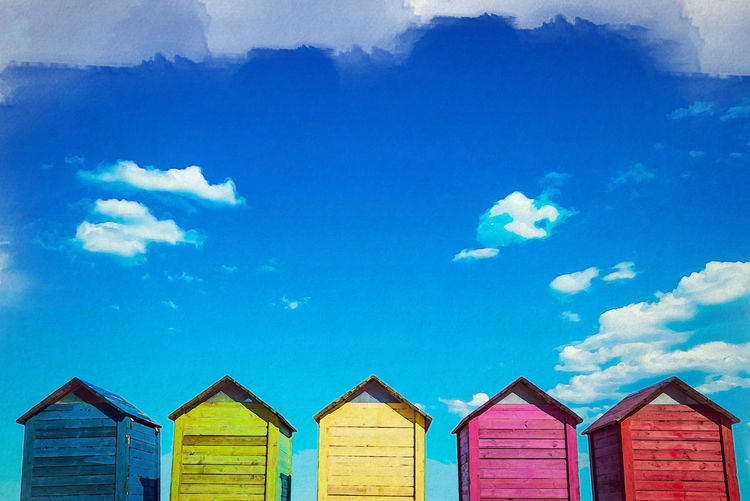 Low angle view of beach huts against sky