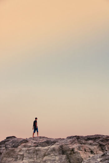 Man standing on rock against sky during sunset