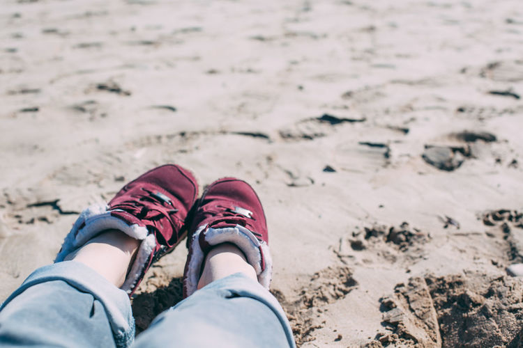 Low section of person wearing shoes on beach