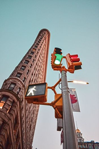 Low Angle View Architecture Building Exterior Built Structure Outdoors Communication Day Clear Sky Guidance No People Illuminated Road Sign Skyscraper City Stoplight Sky Streetphotography Street Photography NYC Photography Flatiron Building Flatironbuilding NYC Street Photography NYC Street NYC Clear Sky
