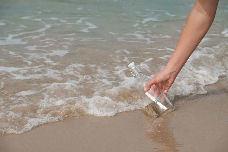 Hand holding a bottle with a letter inserted inside by the sea. Beach Close-up Day Hand Human Body Part Human Hand Letter Low Section Mail Meaaage Nature One Person Outdoors People Real People Sand Sea Sea And Sky Shore Water Wave