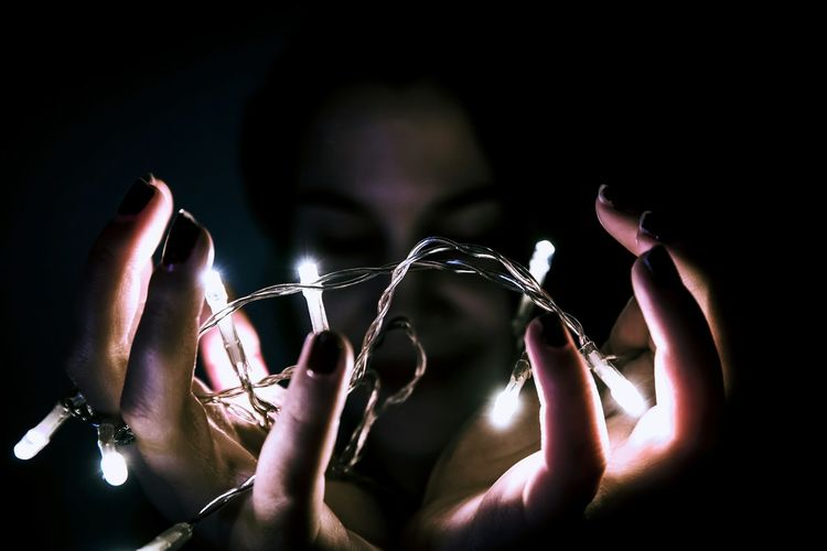 Close-Up Of Woman Holding Illuminated String Lights In Darkroom