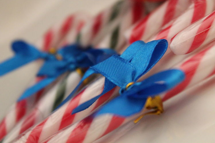 Close-up of blue ribbon tied on candy canes