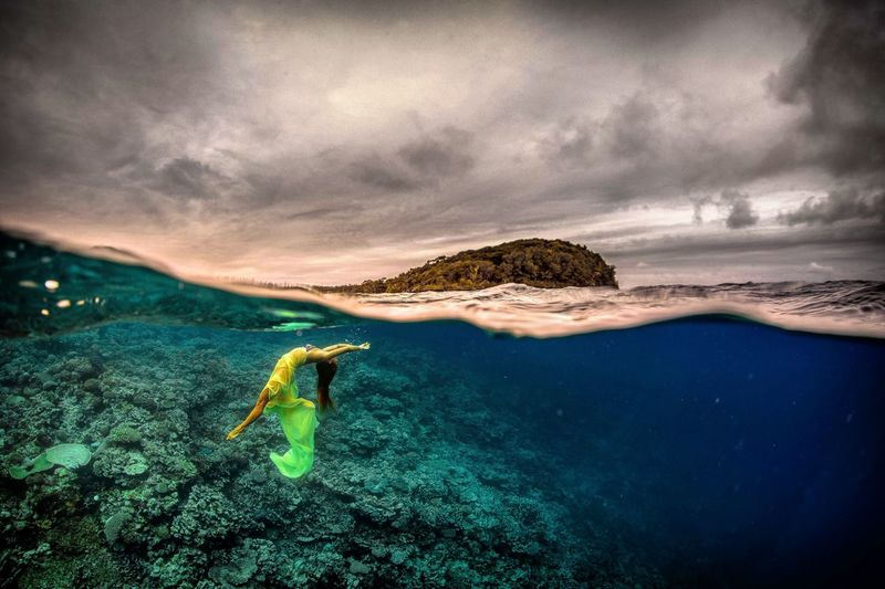 Woman swimming in sea against cloudy sky