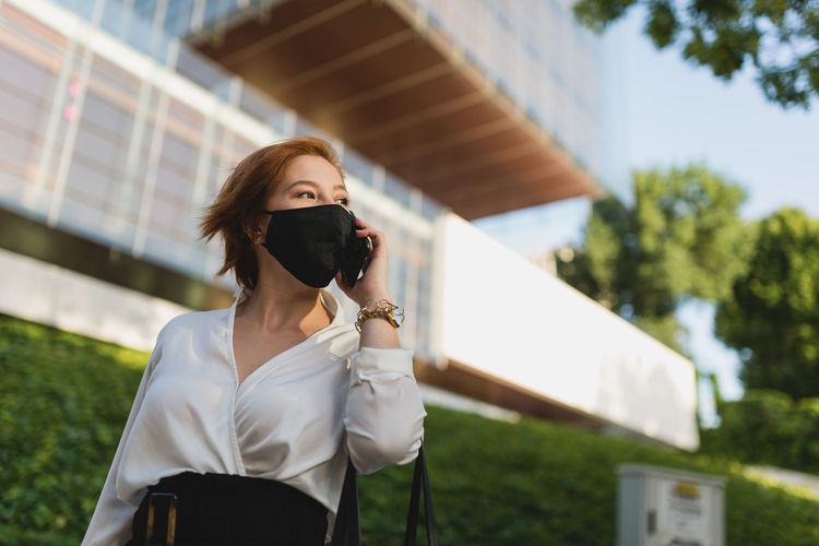Portrait of young woman holding mobile phone standing outdoors