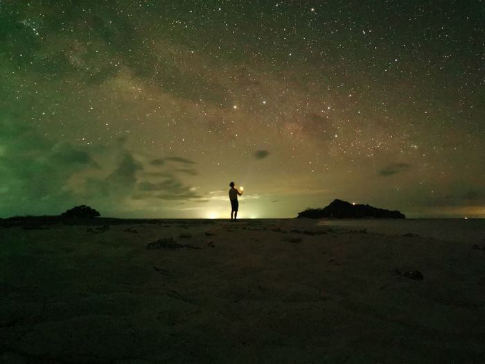 Silhouette person standing on land against star field at night