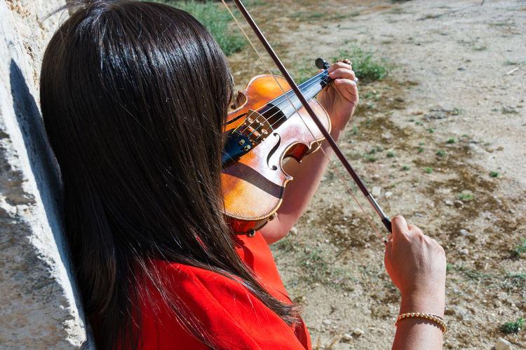 High Angle View Of Woman Playing Violin