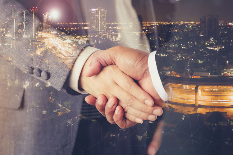 Double exposure of business people handshaking against illuminated city at night