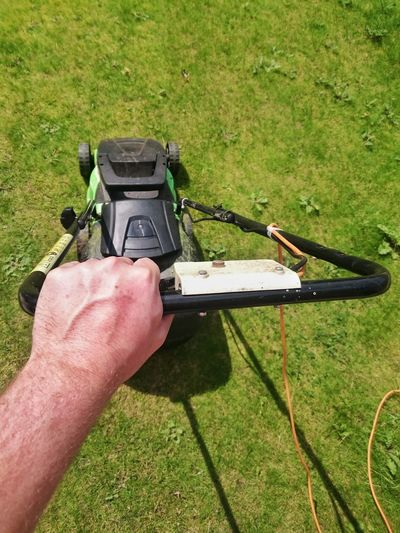 Cropped image of man using lawn mover on grassy field