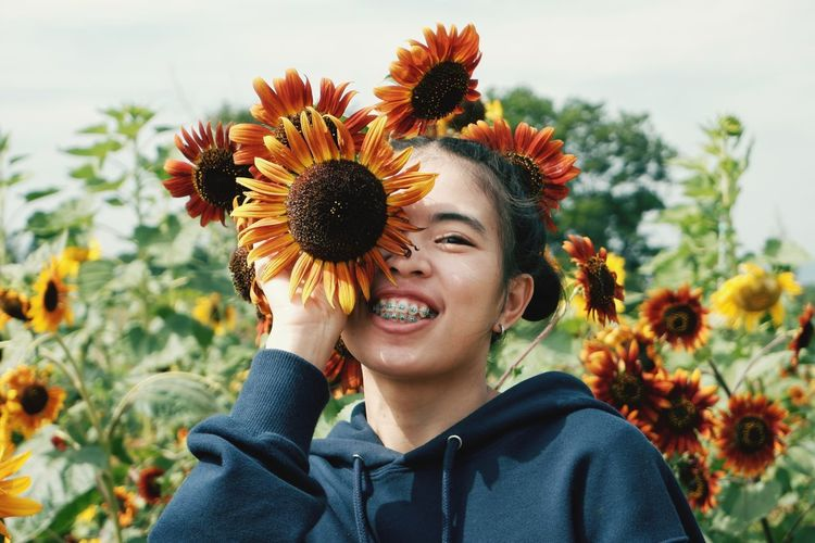 Portrait of smiling woman with sunflower