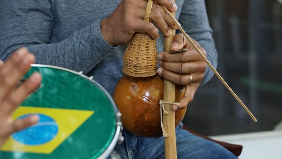 Midsection Of Man Playing Traditional Musical Instrument