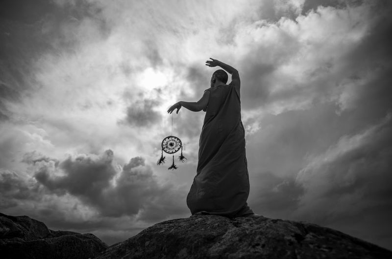 Low angle view of monk holding dream catcher while standing on rock against sky