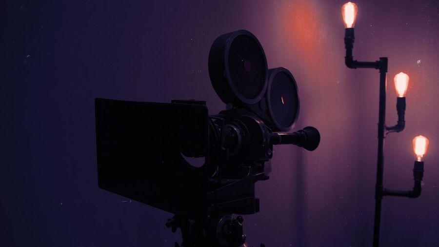 Retro Style Movie Camera In Front Of Illuminated Light Bulb