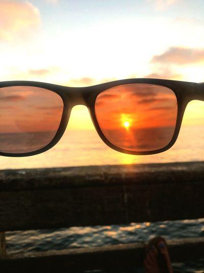 Close-up of sunglasses at sunset