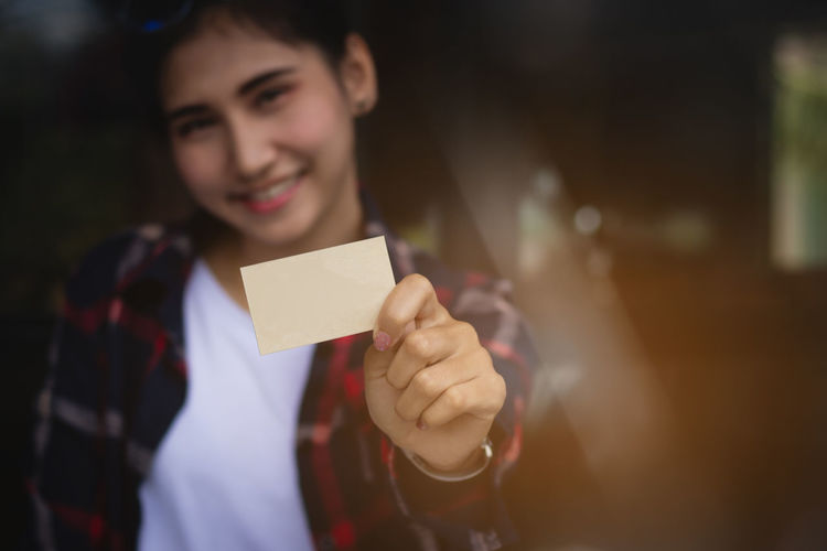 Portrait Of Smiling Young Woman Holding Blank Business Card