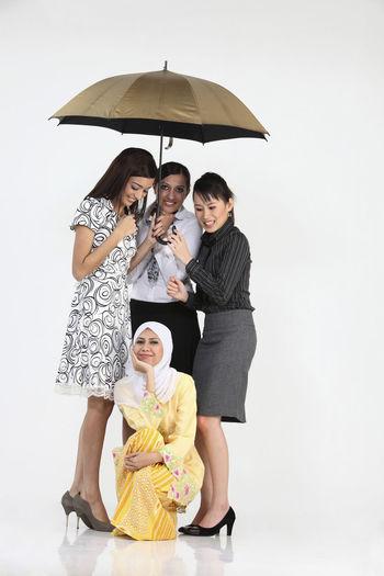Smiling businesswomen with umbrella against white background