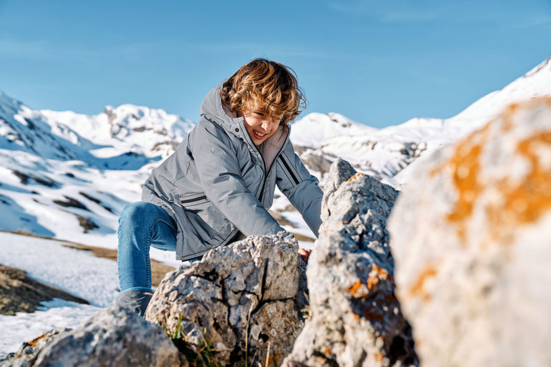Man sitting on rock by snowcapped mountain against sky
