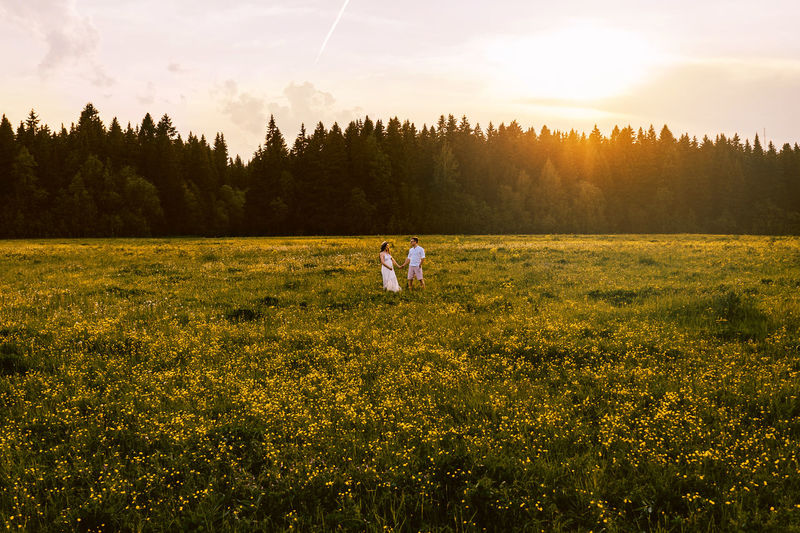 Couple holding hands while standing amidst plants against sky