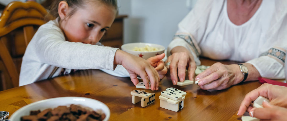 Granddaughter Playing Domino With Grandmother On Table At Home