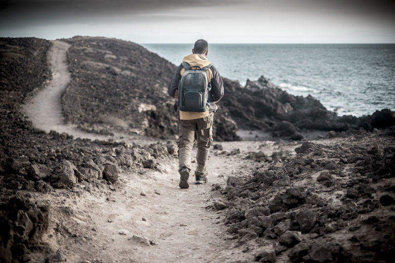 Rear View Of Man With Backpack Walking Towards Sea
