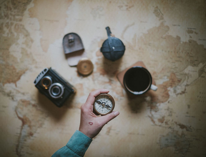 Hand Indoors  One Person High Angle View Directly Above Lifestyles Personal Perspective Cup Compass Planning Travel Planning A Trip Adventure Camera Vintage Camera Tattoo Heart Holding Map World Map
