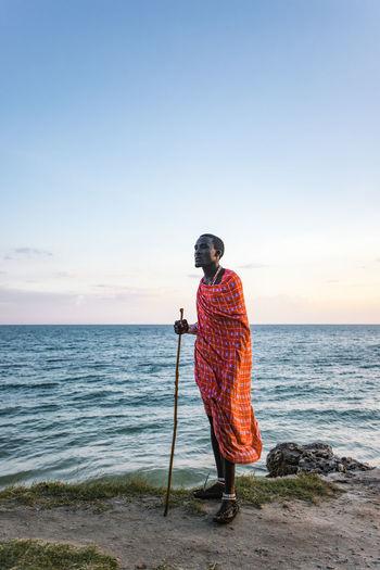 Man standing on beach against clear sky