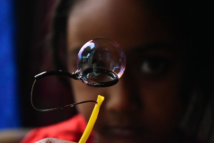 Close-up portrait of girl with bubble wand