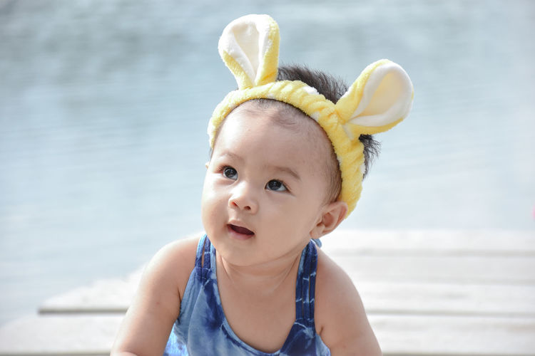 Close-up of cute baby girl wearing headband on pier in lake