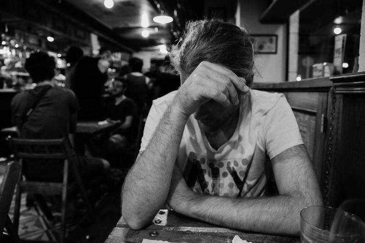 Depressed man sitting at table in bar
