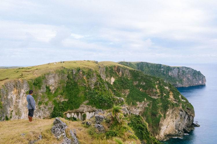 Rear view of rocks on sea against sky