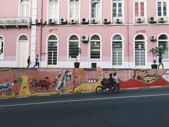 Road by graffiti on wall against pink building in city
