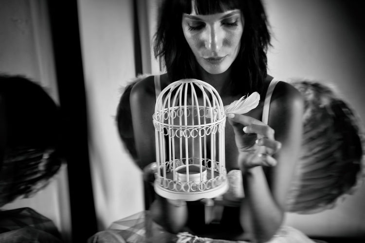 Woman holding feather by bird cage