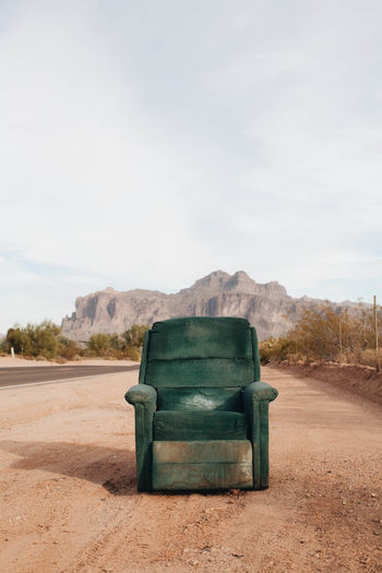 Empty Armchair On Dirt Road Towards Mountain Against Sky