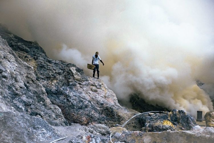 Miner Carrying Basket On Rock Formation Against Smoke