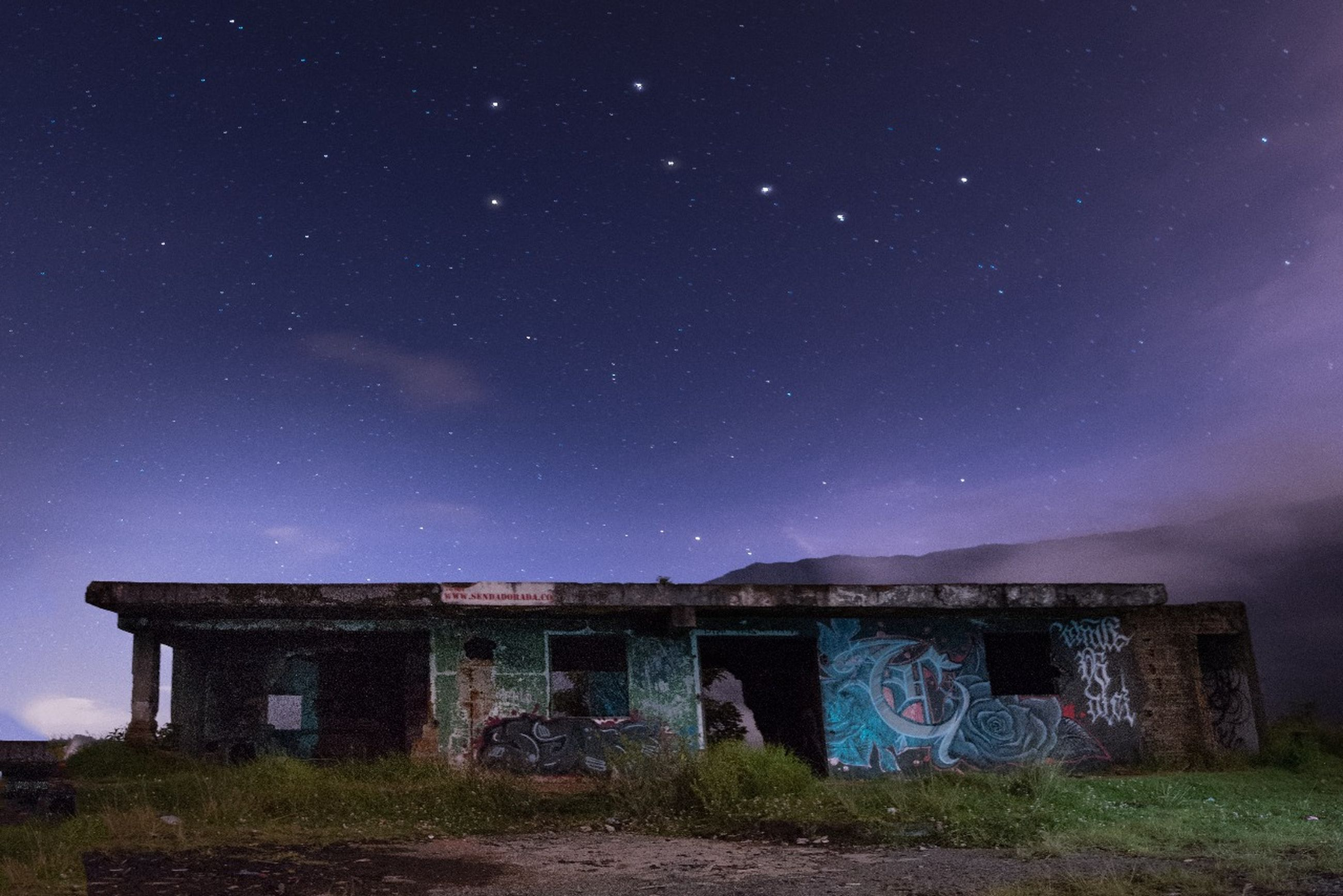 astronomy, sky, architecture, abandoned, built structure, night, no people, outdoors, star - space, building exterior, grass, starry, galaxy, nature