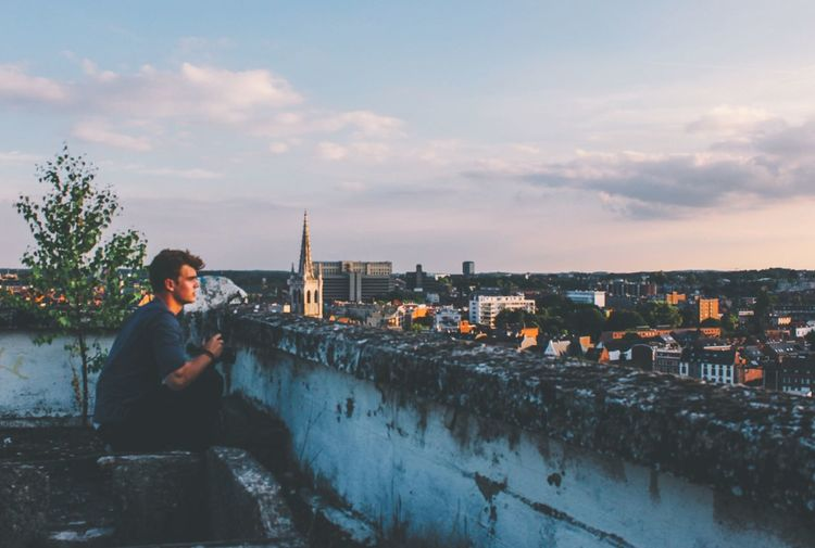 Man sitting by river against sky during sunset