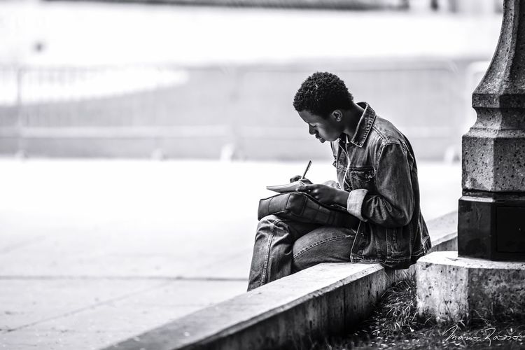 Man Writing In Book While Sitting On Retaining Wall