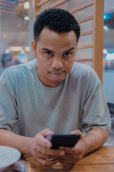 The Portraitist - 2018 EyeEm Awards Casual Clothing Communication Connection Front View Holding Indoors  Leisure Activity Lifestyles Mobile Phone One Person Portable Information Device Portrait Real People Sitting Smart Phone Technology Telephone Wireless Technology Young Men