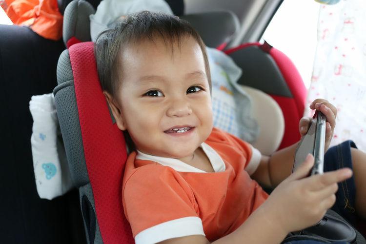 Portrait of cute boy using smart phone in car