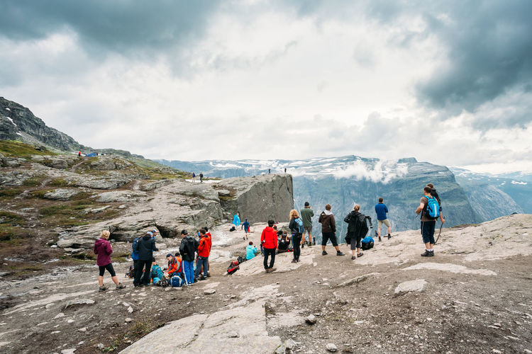 People On Cliff Mountain Against Cloudy Sky