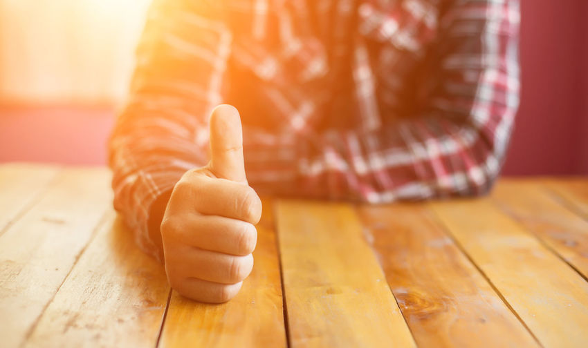 Midsection of person showing thumbs up on table