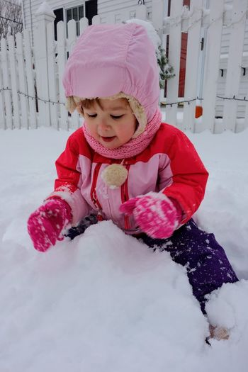 Girl In Warm Clothing Playing While Sitting On Snow Covered Field Against Fence